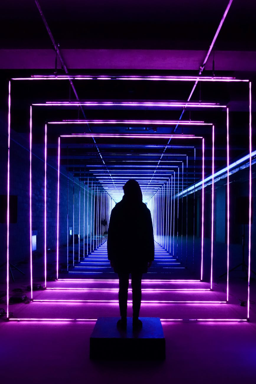 silhouette photo of person standing in neon lit hallway